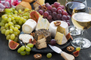 Soft Delicacy Cheeses and Snacks For Wine On A Dark Background, Close-Up
